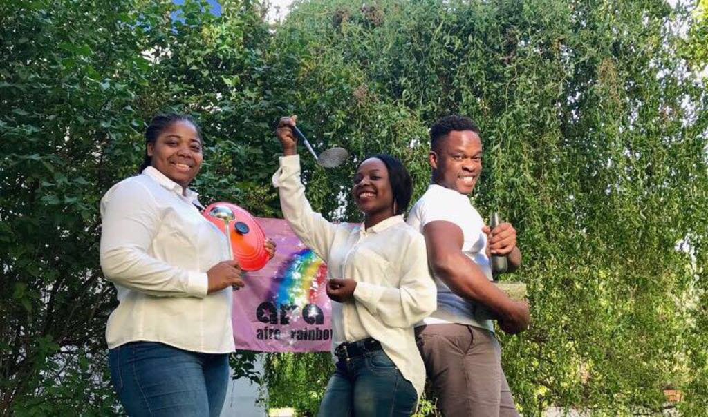 3 members of Afro Rainbow Stop'n Chop holding kitchen utensils